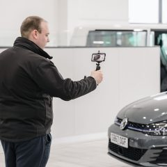 Man recording a CitNOW sales video of a grey car in the showroom