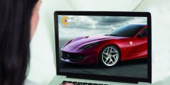Woman looking at her laptop with a red Ferrari on the screen, image taken behind the woman