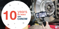 10 years of video with CitNOW, technician taking a CitNOW video in the workshop of a car in the background
