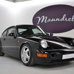 Classic Porsche car in a showroom with the Maundrell logo on the wall in the background