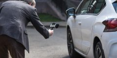 Man in a suit recording a CitNOW sales video outside of a white car