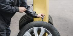 Close up of technician checking tyre tread depth with a tyre gauge whilst recording a CitNOW video