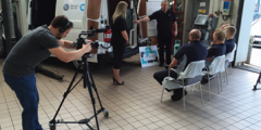 Videographer recording a training day in the workshop, man and woman presenting to three men sat down