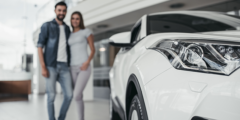 photo of white car, couple in the background out of focus