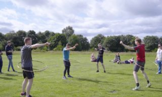 Team activity outdoors on green grass field on sunny day with people using hula hoops around their waists